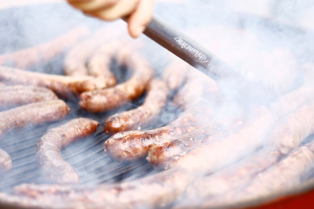 sausages smoking on a barbeque