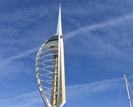 Image of the Spinnaker Tower, Portsmouth with a bluesky backround with streaky white clouds. The tower isa white / cream shade and is structured with a main tall thin spire, and the middle section is strucutred like an oval rib cage.