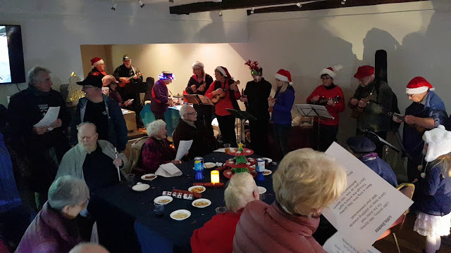 Ukulele group and other guests signing christmas carols in a room. Tables wth festive food and drinks on.