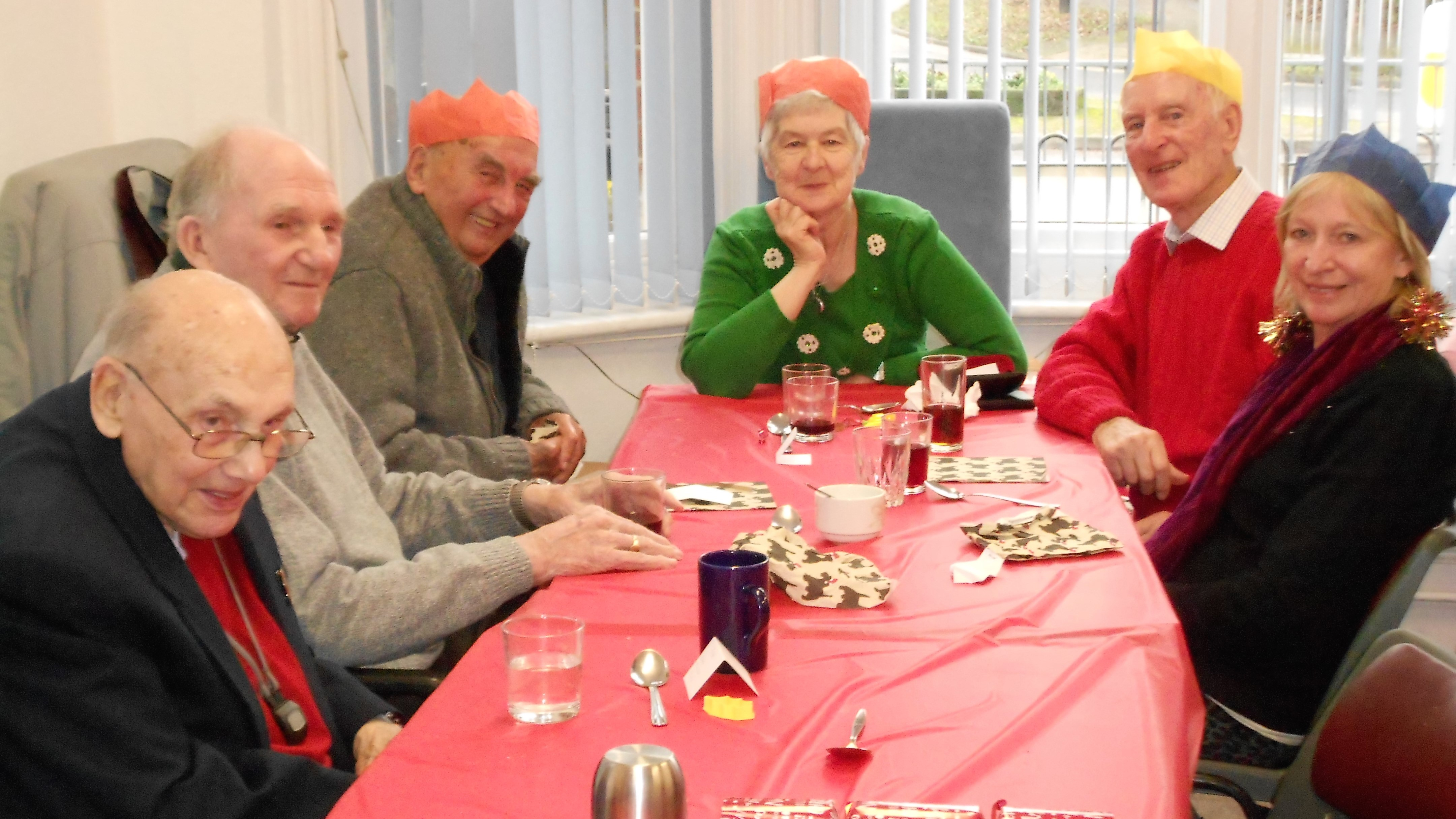 4 men and 2 women sat round a festive decorated table with Christmas hats on