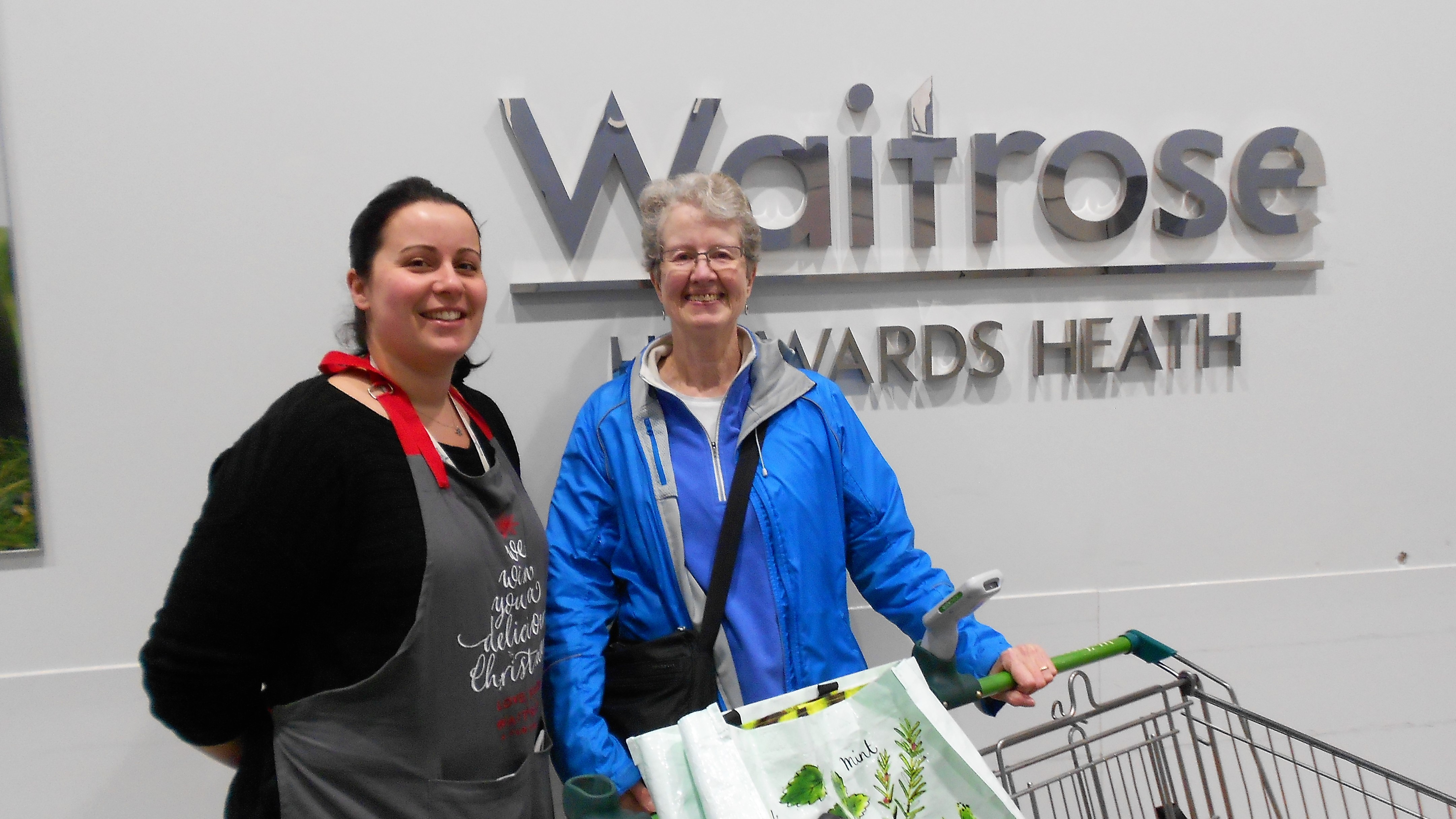 Lady standing with Waitrose staff outside store with trolleys filled with Christmas food