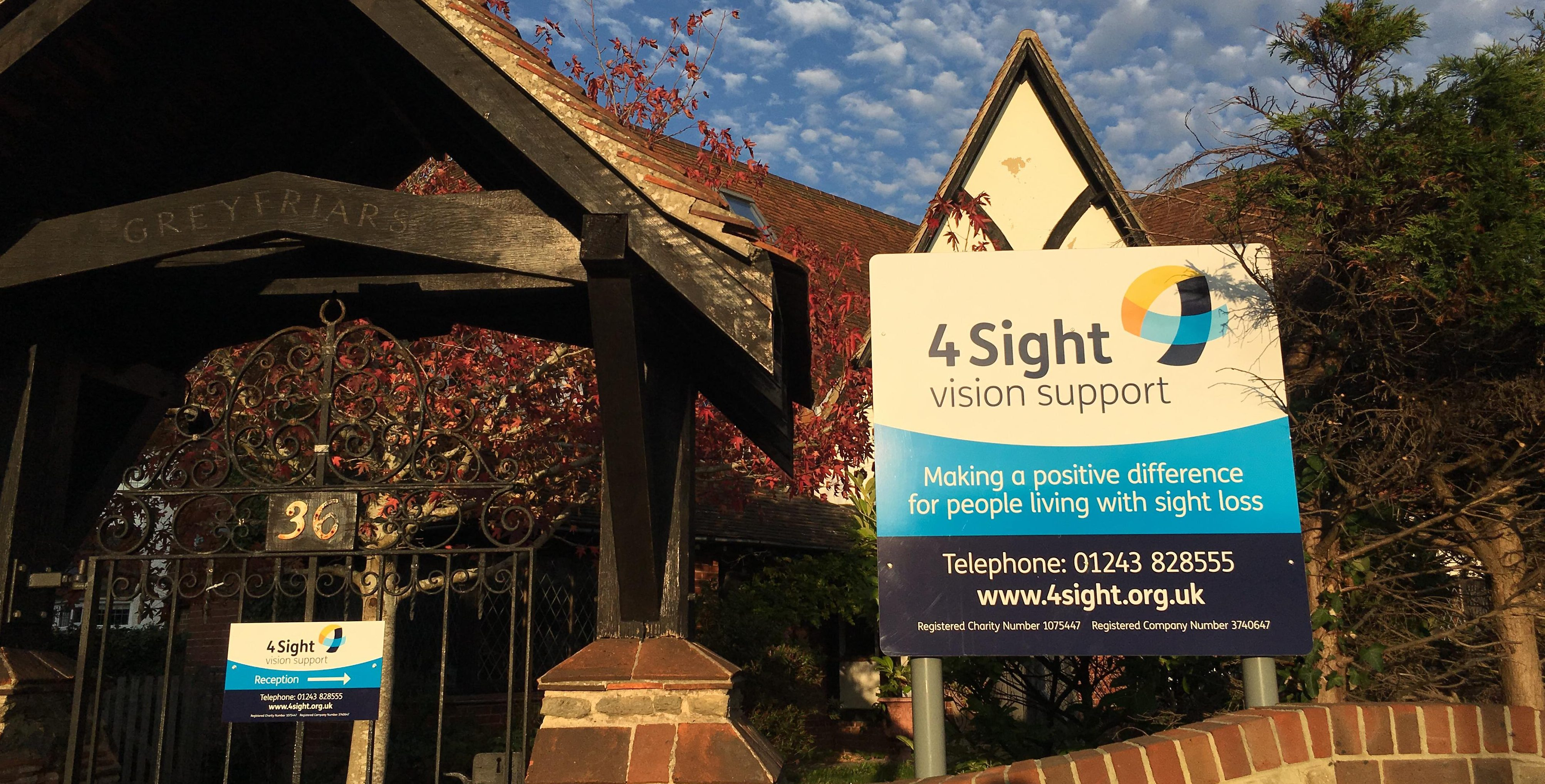arts and crafts centre building with charity signage of 4Sight Vision Support in front. Signange mix of white, blue shades and touches of yellow. Blur sky with clouds in background.