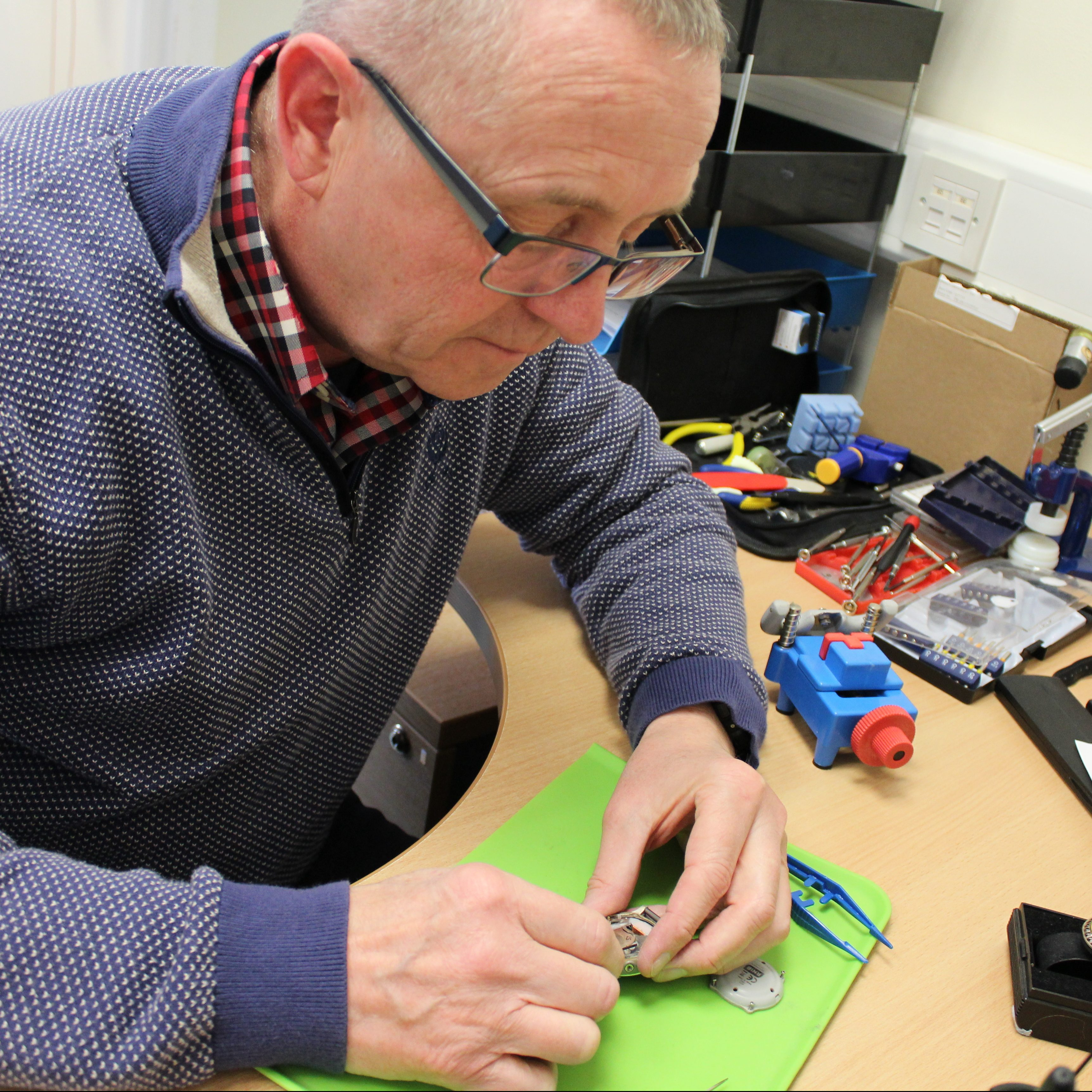 Man opening up a silver watch. Man has grey hair and black framed glasses and is wearing a red checked shirt with blue jumper. On the table with the watch is a green matt and variety of other tools.